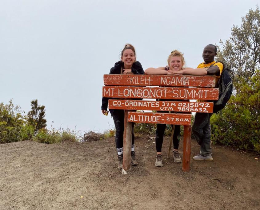 2 meiden en 1 man leunen op bord op de top van de berg