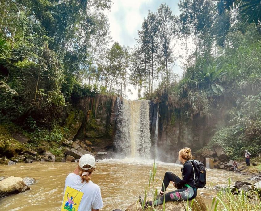 2 meisjs zittend op rots en kijken naar waterval