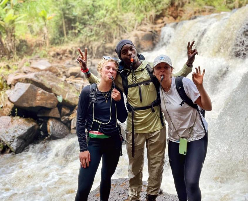 3 mensen op een rots voor een waterval in hikekleding