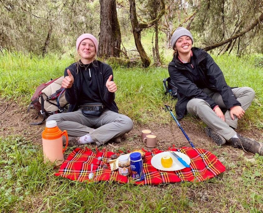 2 meisjes zitten op grond met muts en rood kleed met eten en drinken