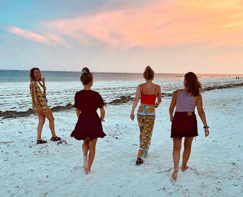 4 meiden lopen over het strand met zonaondergang