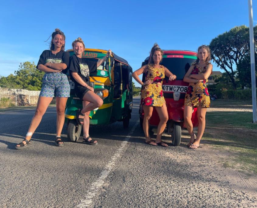 4 meiden staan voor groene en rode tuktuk op weg