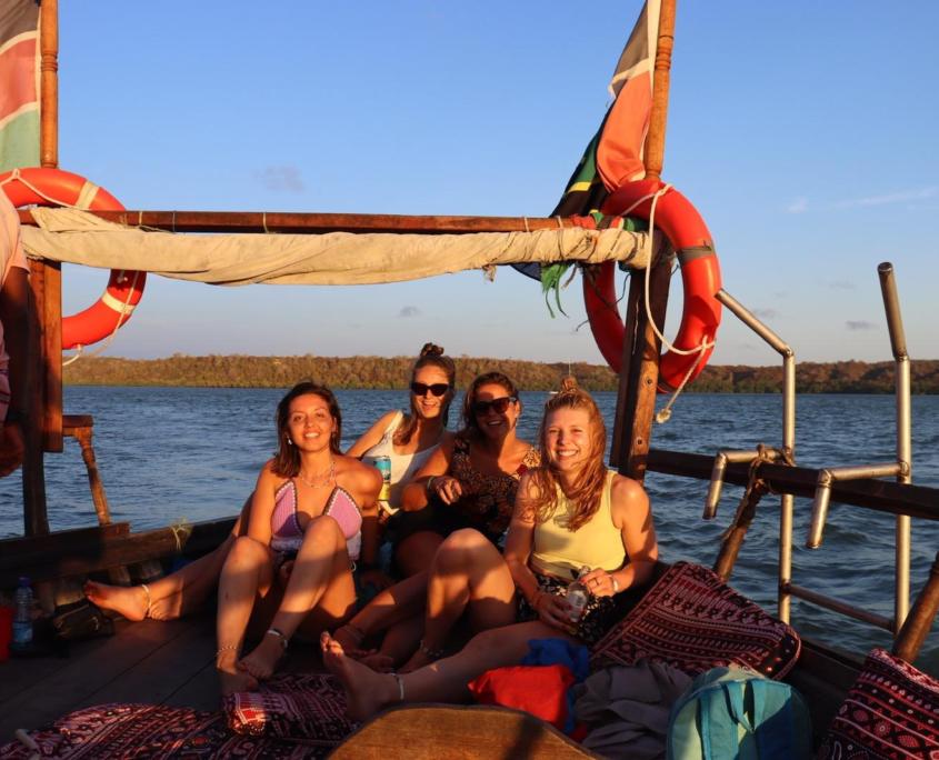 4 meiden op boot met zonsondergang