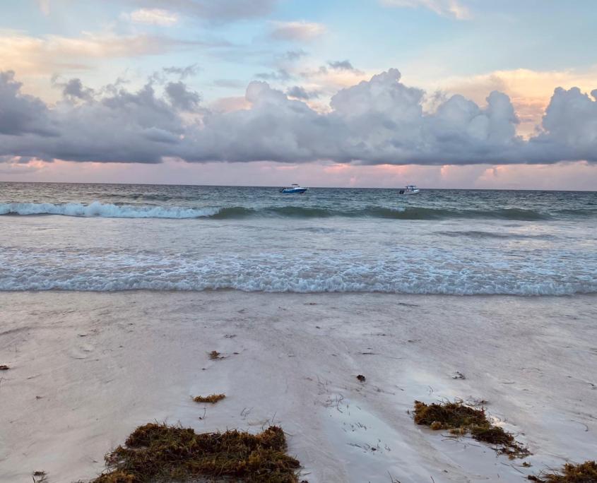 Strand met 2 bootjes en zonsondergang